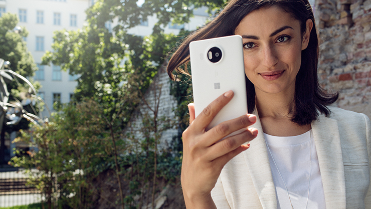 Una mujer mira un smartphone con Windows 10