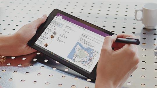 Una mano de mujer sujeta un lápiz y una tableta en cuya pantalla puede verse una pestaña de OneNote con un mapa y texto. Las manos descansan al lado de una taza de café de color blanco a medias y una jarrita de leche.
