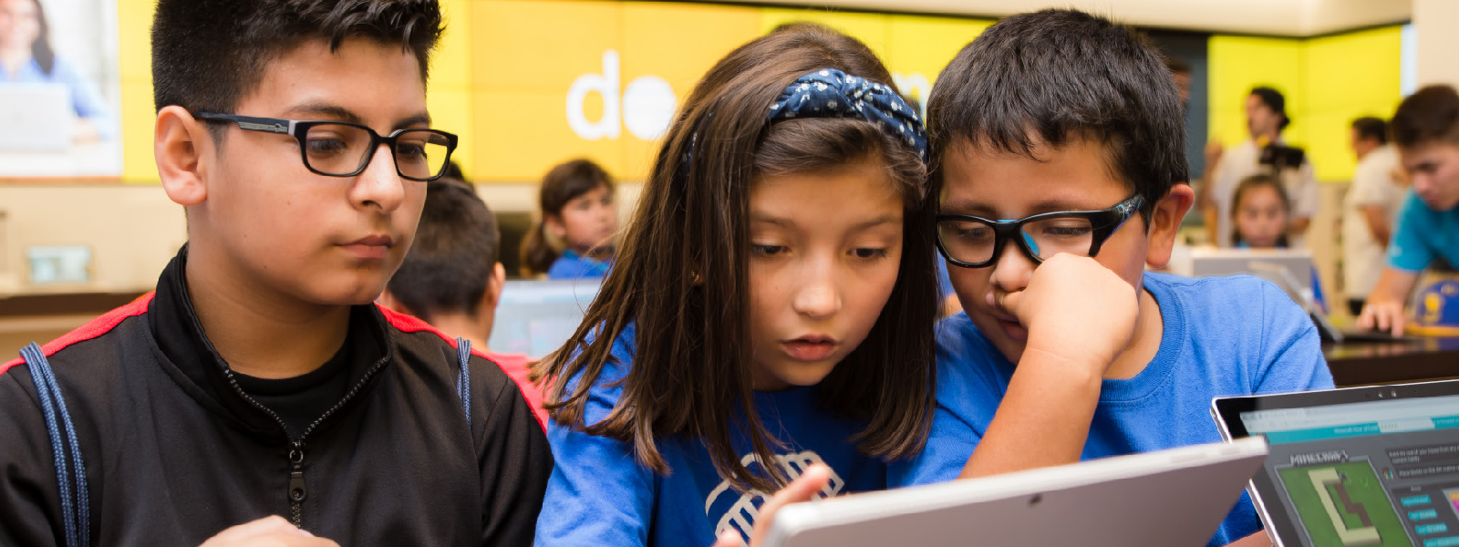 Three young students at Microsoft Store event.