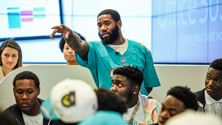 Man in football jersey standing and pointing to front of room, where students are coding.