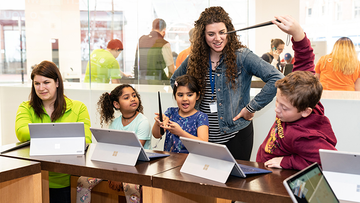 Students and teachers at Microsoft Store Harry Potter Workshop waving wands at Surface device while smiling.