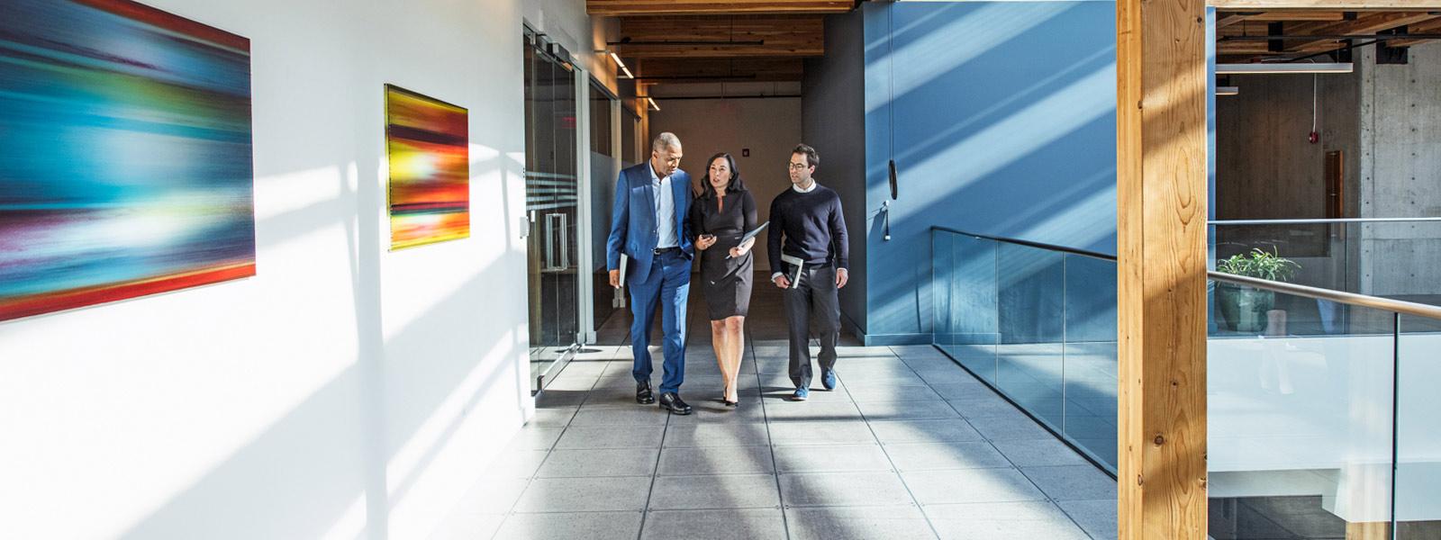 Personas que colaboran en el pasillo de una oficina