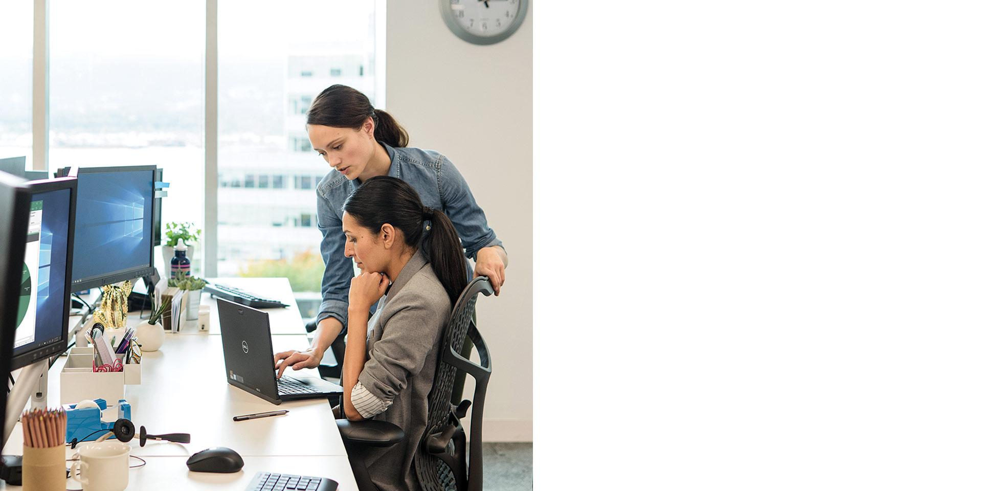 Dos mujeres que consultan una portátil