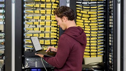 Hombre que usa una portátil en un centro de datos