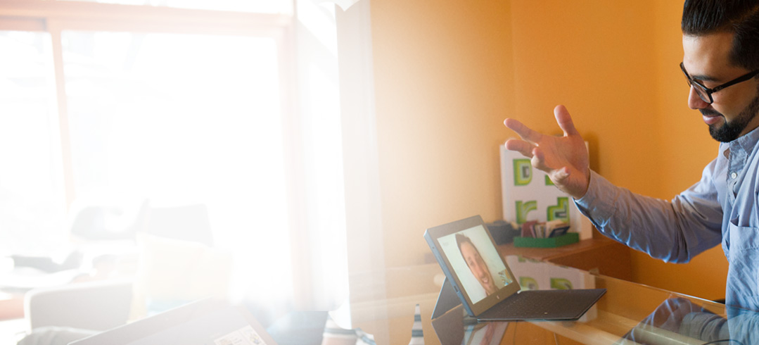Un hombre en una mesa que usa Office 365 para una videoconferencia en una tableta.