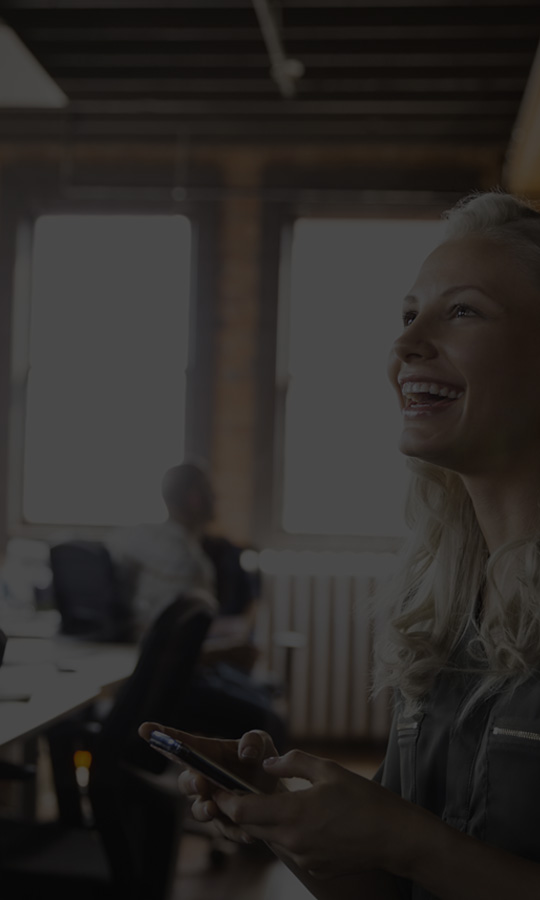Mujer en una oficina mientras usa Office 365 Empresa Essentials en un smartphone.