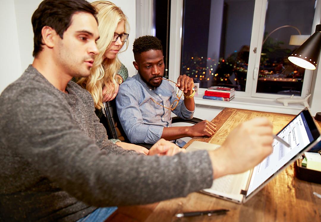 Una mujer y dos hombres en una oficina discutiendo y mirando algo en un portátil