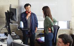 una mujer y un hombre de pie cerca de un escritorio