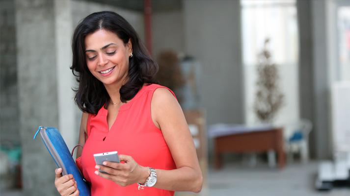 Mobiilsideseadmega kõndiv ja seda vaatav naine.