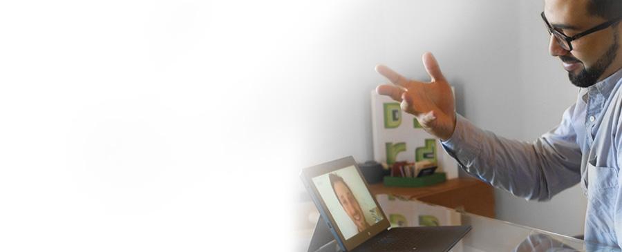 Pöydän ääressä istuva mies videoneuvottelussa tablettia ja Skype for Businessia käyttäen