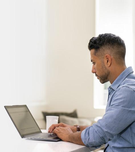 Mies käyttää kannettavaa tietokonetta