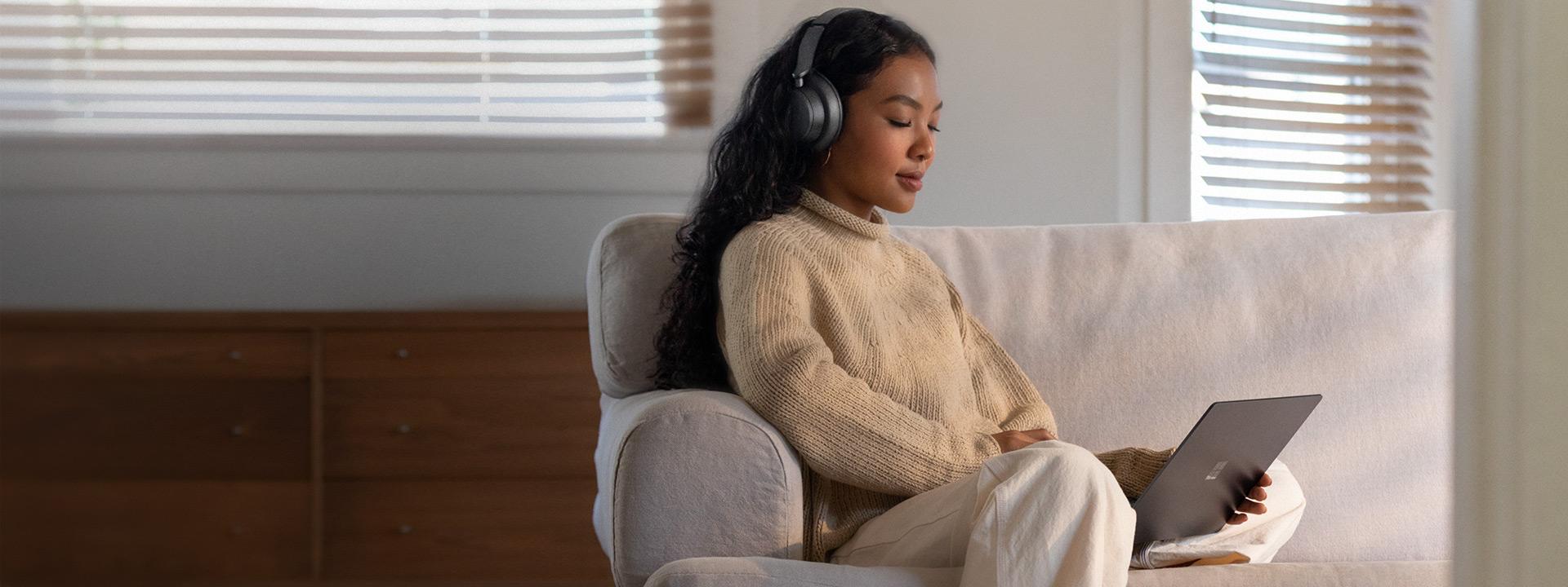 Nainen työskentelee kotona sohvalla käyttämällä Surface Laptop 3:a ja Surface Headphones 2:ta