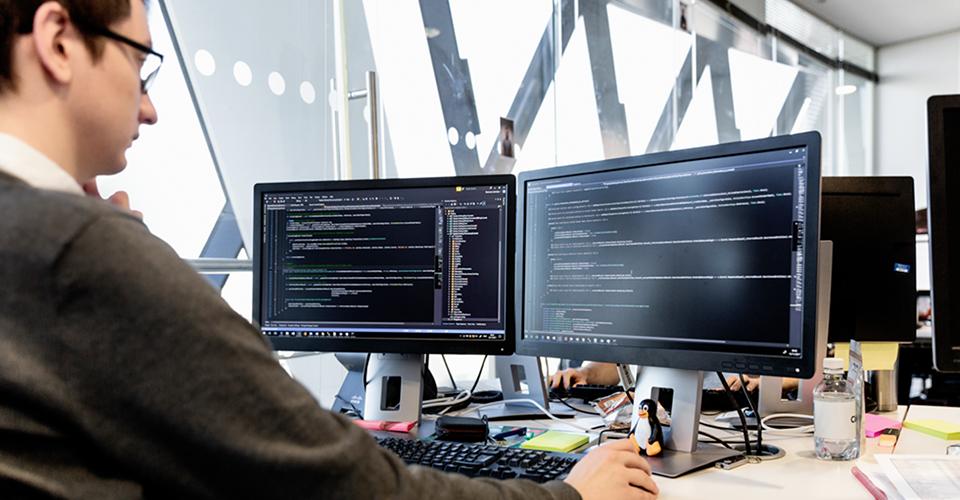 Valokuva henkilöstä jaetussa toimistotilassa työskentelemässä työpöydän ääressä, jolla on kaksi suurta näyttöä, joissa näkyy tietoja