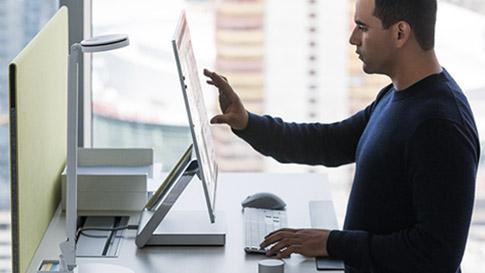 Mies käyttämässä Surface Studion kosketusnäyttöä.