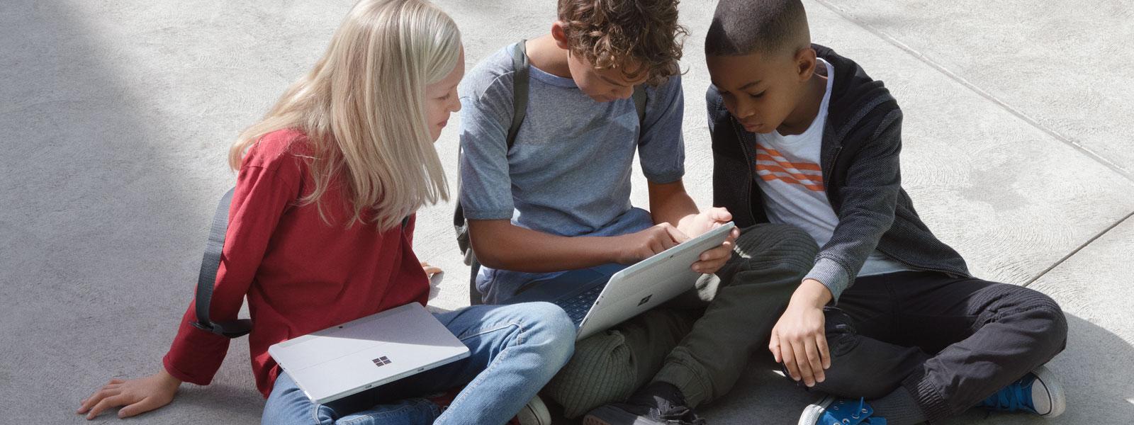 Kolme opiskelijaa istumassa pihalla Surface Go sylissään