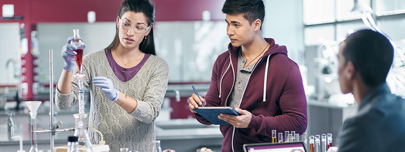 Kolme opiskelijaa kemian laboratoriossa, yksi käyttää Surface Pro 4:ää tablettitilassa ja toinen kannettavan tietokoneen tilassa.