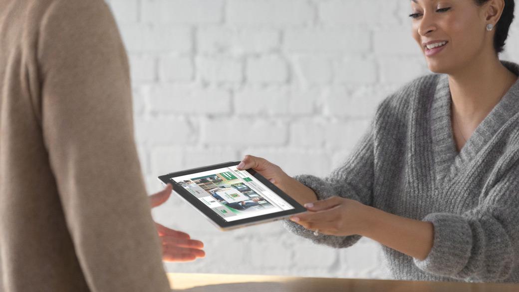 Nainen pitää käsissään Surface-laitetta puhuessaan asiakkaan kanssa.