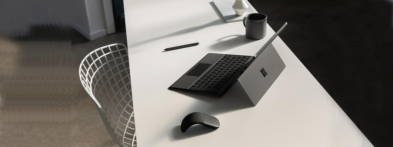 Surface Pro 6 pöydällä kannettavan tietokoneen tilassa yhdessä Surface Type Coverin, Surface-kynän ja Surface Arc Mouse -hiiren kanssa