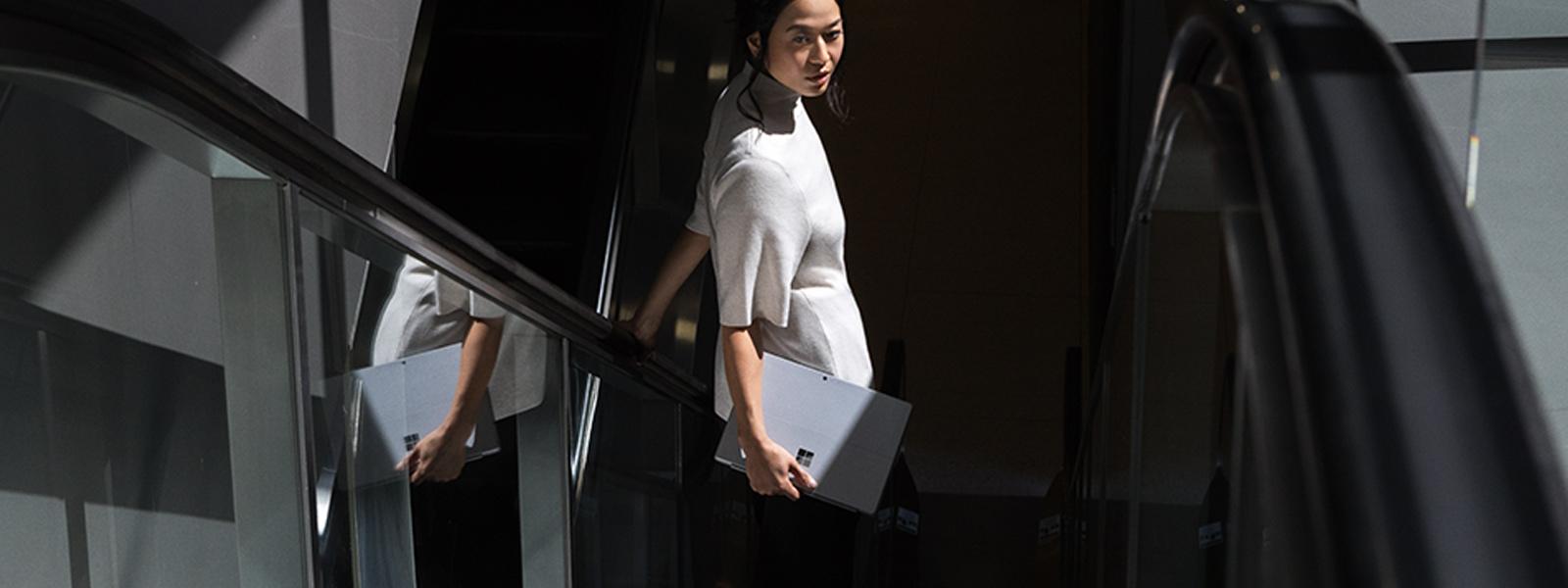 Nainen laskeutuu liukuportaita Surface Pro kädessään.