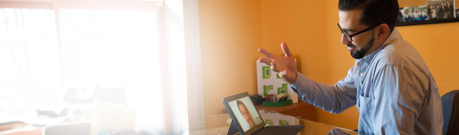 Pöydän ääressä istuva mies videoneuvottelussa tablettia ja Office 365:tä käyttäen
