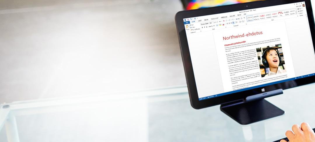 Työntekijä kirjoittamassa näppäimistöllä, Word-asiakirja näytössä.