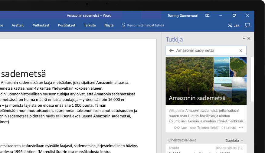 Kannettava tietokone, jossa näkyy Word-asiakirja ja lähinäkymä Amazonin sademetsää käsittelevästä artikkelista Researcher-toiminnossa