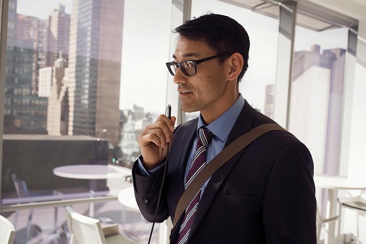 Henkilö toimistossa puhumassa mobiililaitteeseen