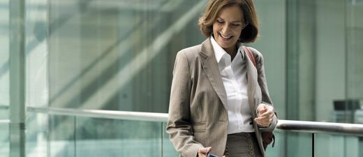 Nainen katsoo alaspäin puhelintaan, tietoja Exchange Online Archivingin ominaisuuksista ja hinnoista