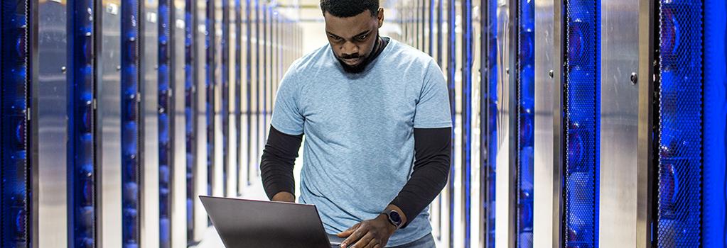 Mies tekee töitä kannettavalla tietokoneella palvelinhuoneessa