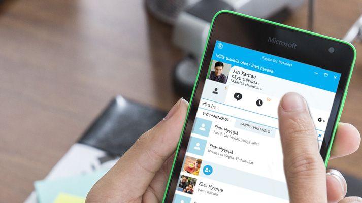 Kädessä oleva mobiililaite, jossa puhelu soitetaan Skypellä