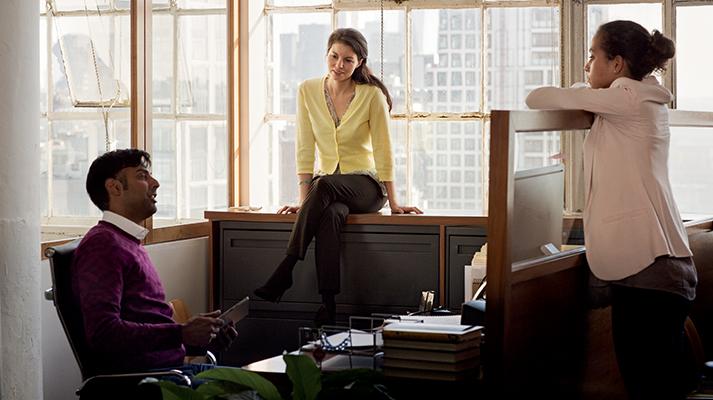 Kolme henkilöä keskustelee avoimessa toimistotilassa
