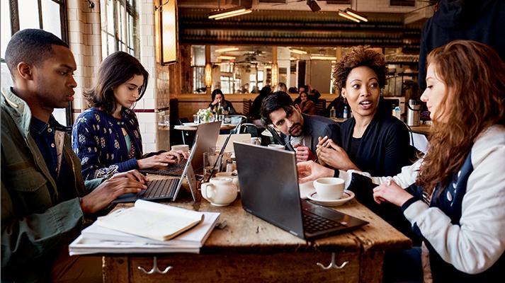 Ryhmä henkilöitä istuu kahvilassa ja työskentelee kannettavilla tietokoneilla