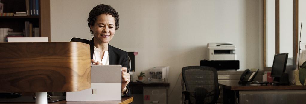 Nainen hymyilee työskennellessään toimistossa Surface-laitteella