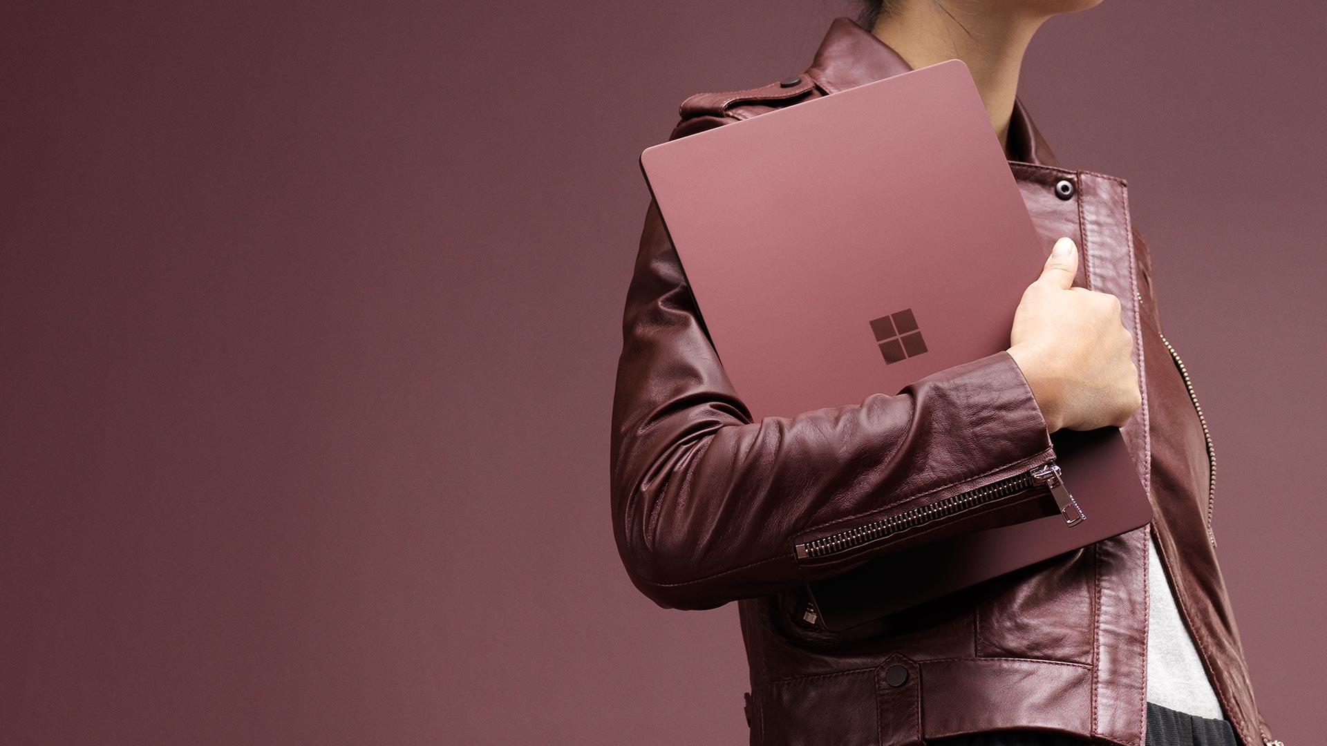 Nainen kantaa viininpunaista Surface Laptopia