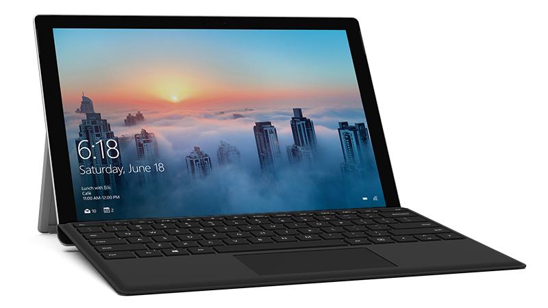 Musta Surface Pro 4 Type Cover kiinnitettynä Surface Pro -laitteeseen, vinokuva kaupunkiympäristössä