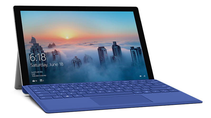 Sininen Surface Pro 4 Type Cover kiinnitettynä Surface Pro -laitteeseen, vinokuva kaupunkiympäristössä