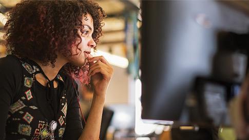 Nainen työskentelee pöytänsä ääressä.