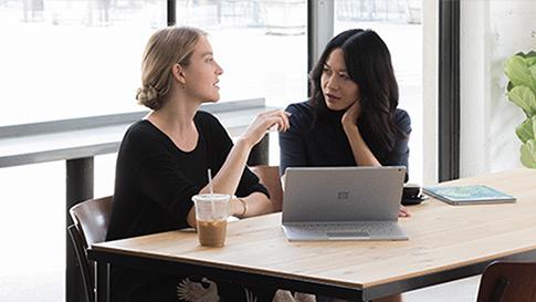 Kaksi naista istumassa kahvilassa edessään katselutilassa oleva Surface Book 2