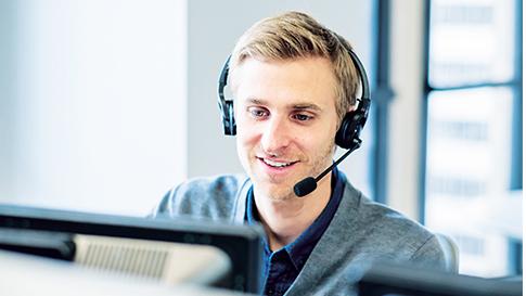 Mies istuu pöytäkoneen ääressä ja käyttää kuulokemikrofonia.