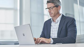 Mies työskentelemässä Surface Laptopin kanssa.