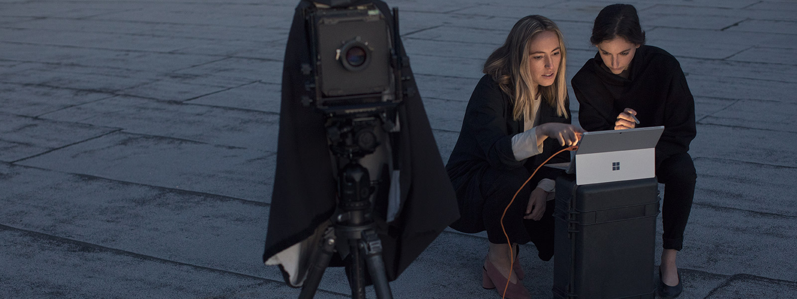 Kaksi videokuvaajaa käyttämässä Surface Pro -laitetta kuvattujen otosten tarkastamiseen