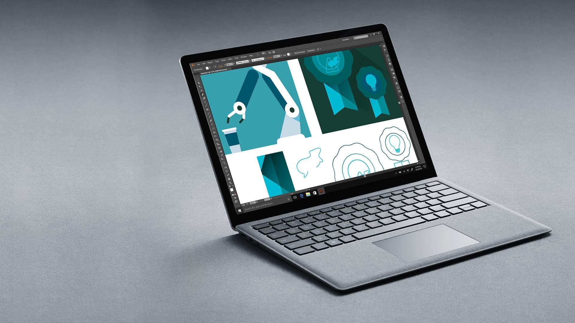 Platinanvärinen Surface Laptop, jonka näytössä on Adobe Illustrator.