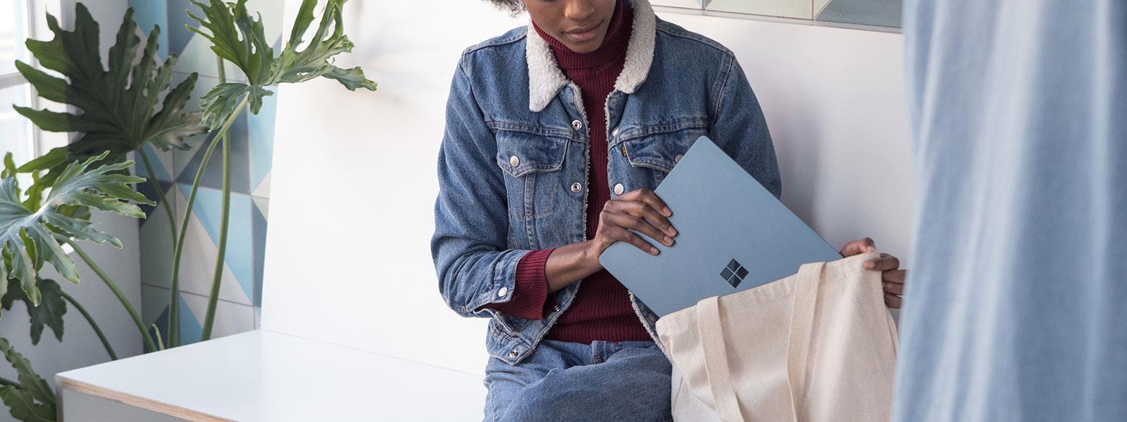 Nainen asettamassa Surface Laptopia laukkuun.
