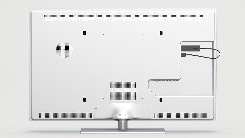 Yksityiskohtainen kuva Wireless Display Adapterista näyttölaitteen takasivulle liitettynä.