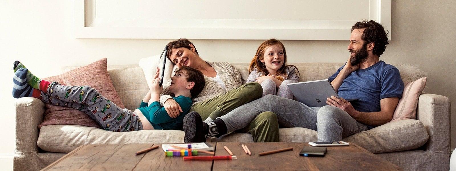 Perhe makaamassa sohvalla