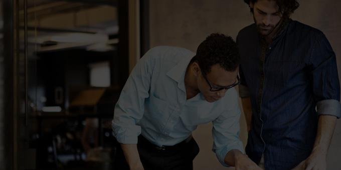 Deux hommes en train de discuter et de travailler dans un bureau avec Office365 EntrepriseE4.