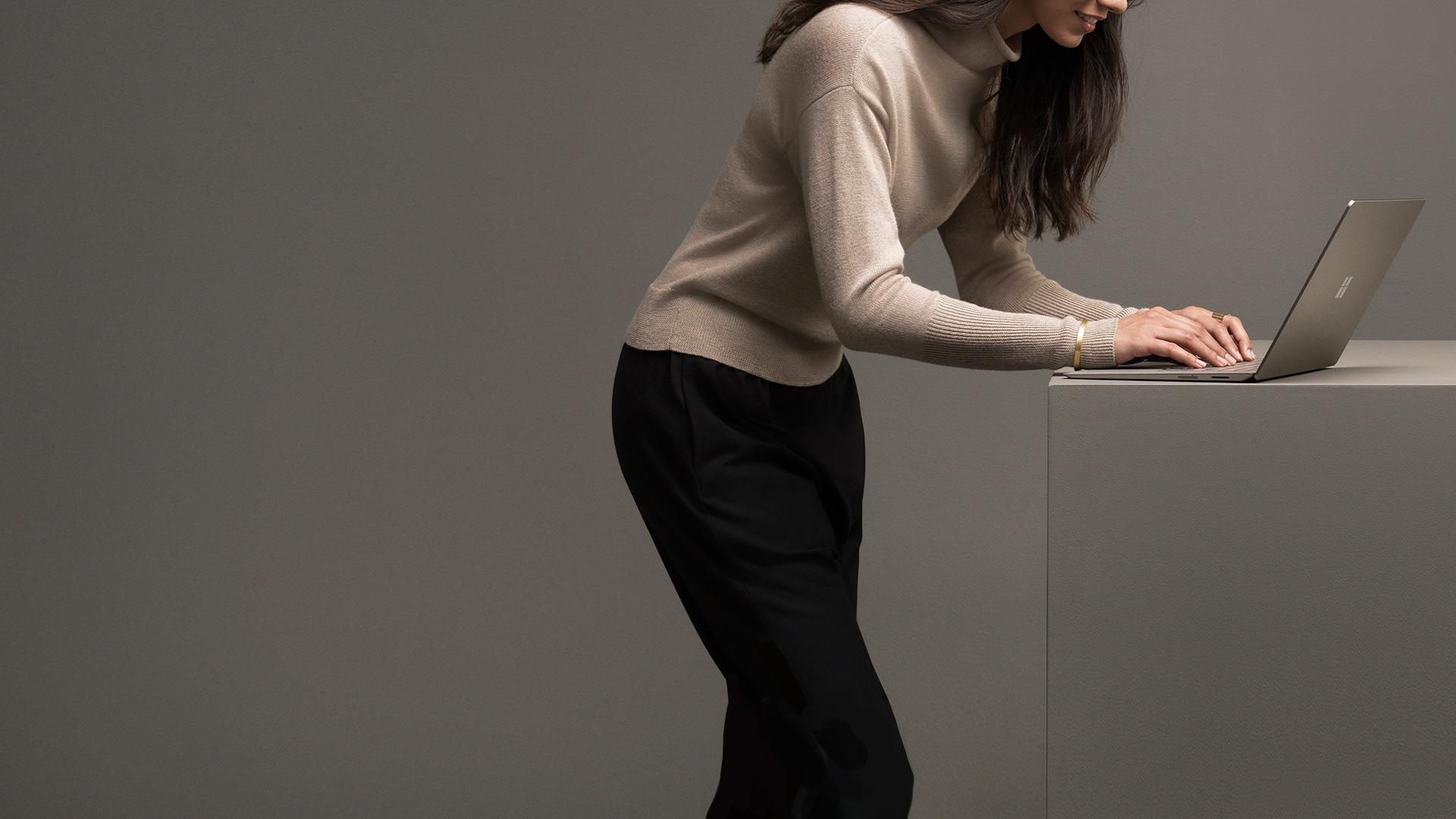 Woman typing on the Graphite Gold Surface Laptop.
