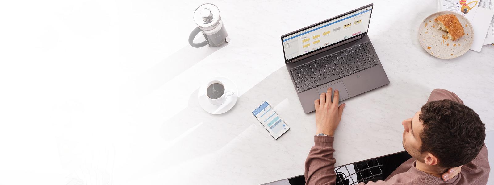Un homme assis avec un ordinateur portable Windows et son téléphone à côté de lui