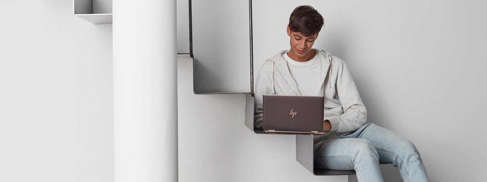 Un étudiant assis dans les escaliers tout en travaillant sur un ordinateur portable