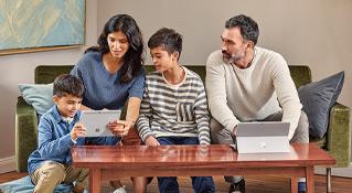 Un homme, une femme et deux garçons utilisant deux ordinateurs Microsoft Surface sur un canapé à la maison